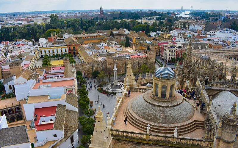"""""""I took this photo walking up to the top of la Giralda, and I love it because you can see so many iconic parts of the city. To the far left in the mid and foreground is the Juderia, and in the very center is the Alcazar. Beyond the Alcazar in the distance, you can see the towers of the Plaza de Espana. Between the Alcazar and the Plaza de Espana you can see the top of the Plaza de Toros. In front of the Alcazar is the Plaza del Triunfo, with the Monumento a la Imaculada, and to the right of the Plaza are numerous historical buildings near la Avenida de la Constitución"""" - Elizabeth Henning Spring 2020 Cityscape Sevilla, Spain"""